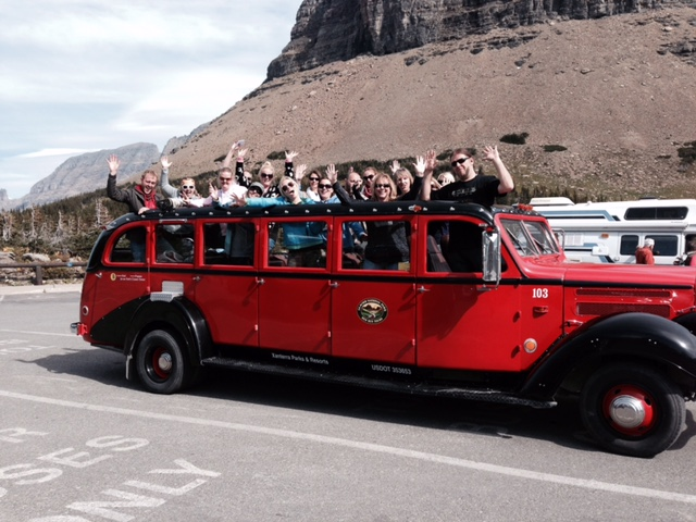 Red bus tour stop at the top of Logan Pass.